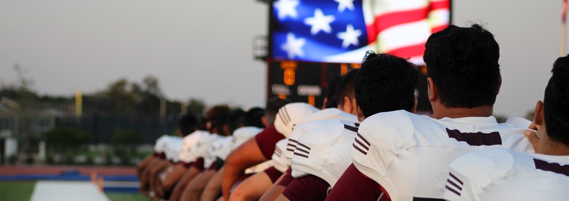 Picture of the football team and American flag.
