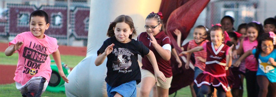 Elementary students with perfect attendance run out onto the field.